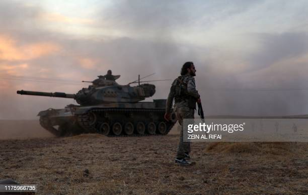 Turkey-backed Syrian fighters gather around a Turkish army US-made M60 tank in the northern outskirts of the Syrian city of Manbij near the Turkish...