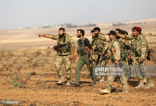 Turkeybacked Syrian fighters gather at a position east of the northeastern Syrian town of Ras alAin facing positions held by fighters from the Syrian...