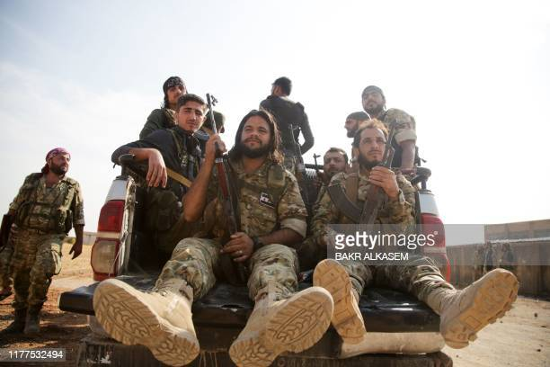 Turkey-backed Syrian fighters gather on a road between the northern Syrian towns of Tal Abyad and Kobane on October 22 hours before a deadline for...