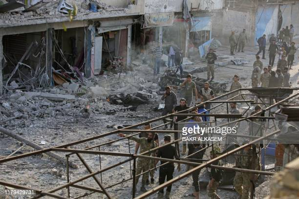 Turkey-backed Syrian fighters inspect the site of a car bomb explosion in the northern Syrian Kurdish town of Tal Abyad, on the border with Turkey,...