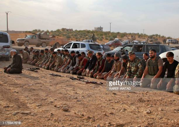 Turkey-backed Syrian fighters kneel to pray as they gather with Turkish troops near the village of Qirata on the outskirts of the northern city of...
