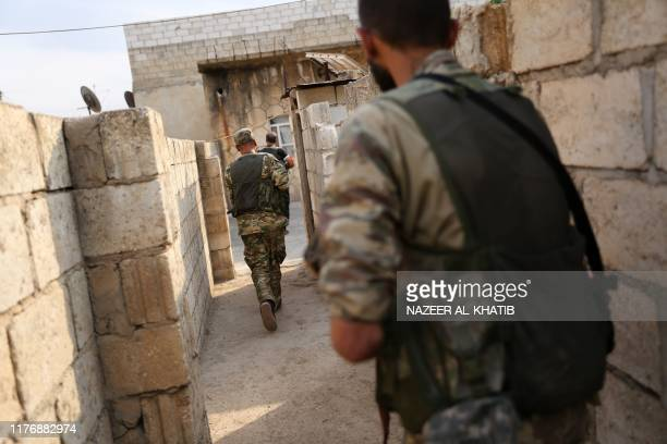 Turkeybacked Syrian fighters leave a house that they are using as a postition in the Syrian border town of Ras alAin on October 19 2019 Turkey's...