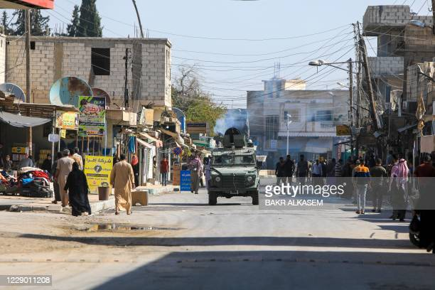 Turkey-backed Syrian fighters patrol a street in the rebel-controlled town of Tal Abyad in Syria's northern Raqa province, on October 11, 2020. - UN...