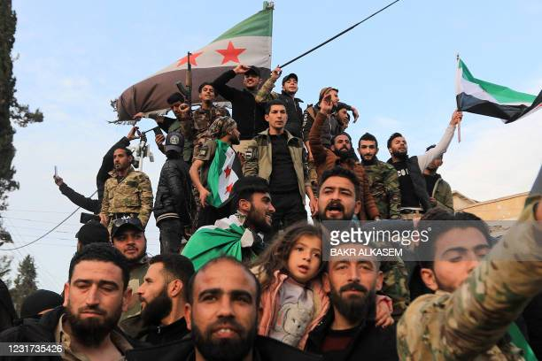 Turkey-backed Syrian fighters pose together for a group photo with flags of the Syrian opposition in the rebel-controlled town of Tal Abyad in...