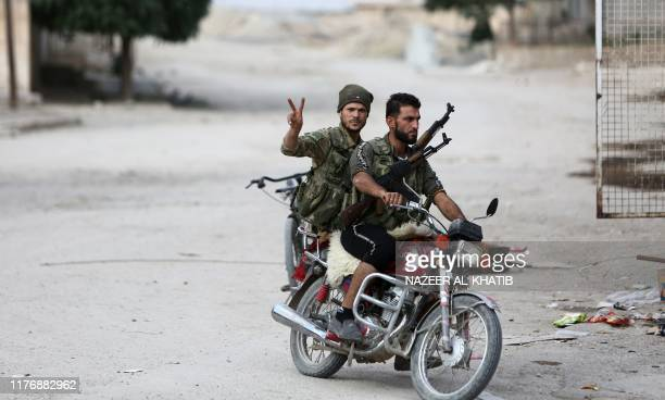 Turkey-backed Syrian fighters ride a motorcycle at a position that they are holding in the Syrian border town of Ras al-Ain on October 19, 2019. -...