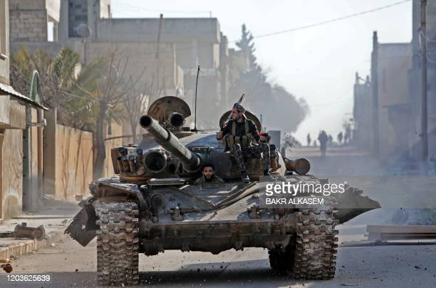 Turkey-backed Syrian fighters ride a tank in the town of Saraqib in the eastern part of the Idlib province in northwestern Syria, on February 27,...