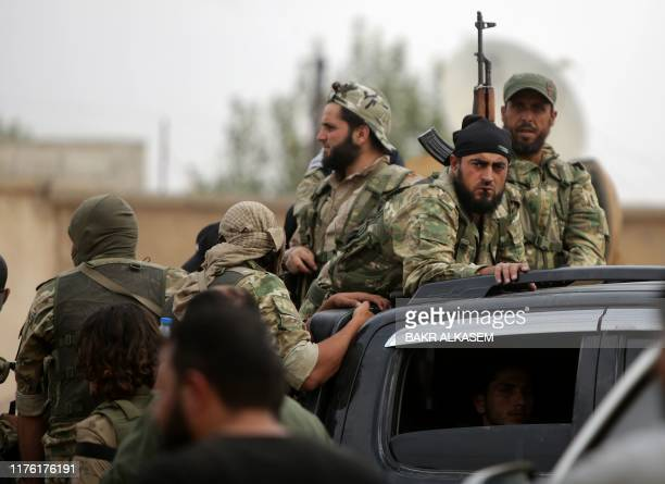 Turkeybacked Syrian fighters ride in the back of pickup trucks on the road between the Syrian towns of Tal Abyad and Kobane on the Turkish border on...