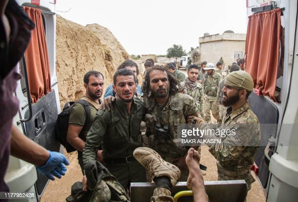 Turkey-backed Syrian fighters rush a comrade into an ambulance after sustaining wounds from a mine that exploded when they took over the area around...