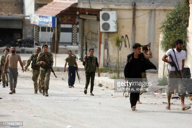 Turkeybacked Syrian fighters walk in a street near a position that they are holding in the Syrian border town of Ras alAin on October 19 2019...