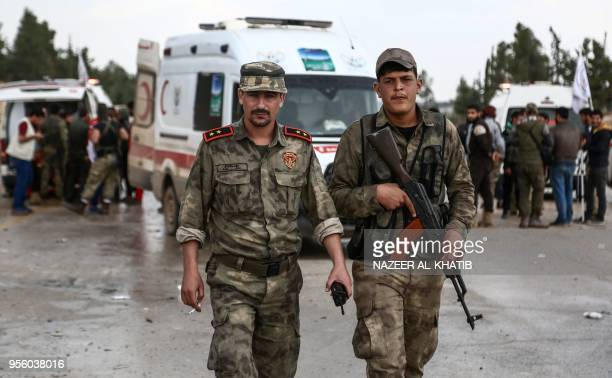 Turkeybacked Syrian fighters walk in Abu alZandin checkpoint near alBab in northern Syria on May 8 as a convoy of buses carrying people evacuated...