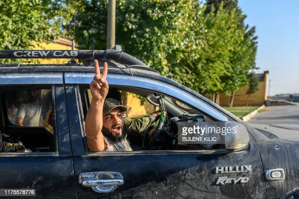 Turkey-backed Syrian National Army fighters celebrate from their car on October 13, 2019 in Akcakale SNA seized today the Syrian border city of Tal...
