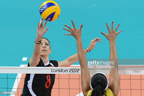 Turkey's Bahar Toksoy spikes as Brazil's Paula Pequeno attempts to block during the women's volleyball match between Turkey and Brazil in the 2012...