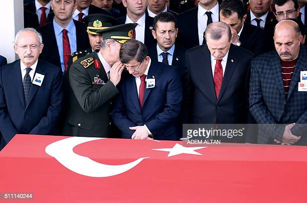 Turkey's Chief of Staff General Hulusi Akar talks with Turkey's Prime Minister Ahmet Davutoglu as they attend with Turkey's President Recep Tayyip...