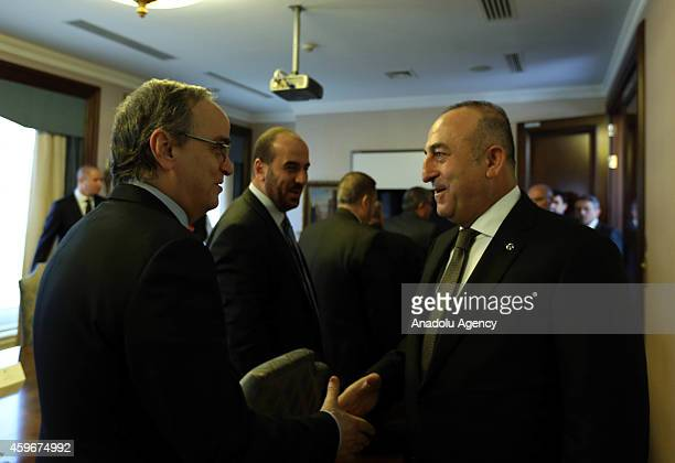 Turkey's Foreign Affairs Minister Mevlut Cavusoglu shakes hands with President of the Syrian National Coalition Hadi alBahra following a meeting at...