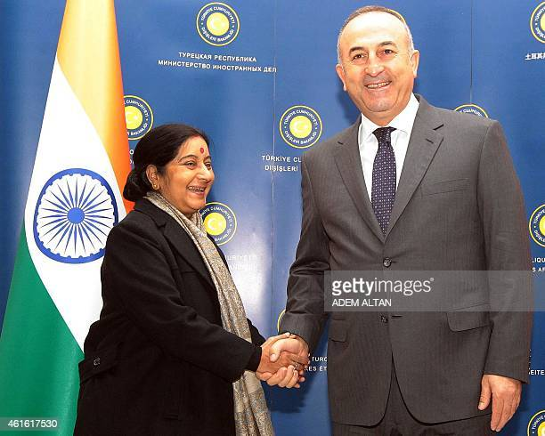 Turkey's Foreign Affairs minister Mevlut Cavusoglu shakes hands with his Indian counterpart Sushma Swaraj prior to a meeting in Ankara on January 16...