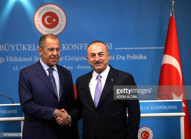 Turkey's Foreign Minister Mevlut Cavusoglu and his Russian counterpart Sergei Lavrov shake hands during a joint press conference following their...