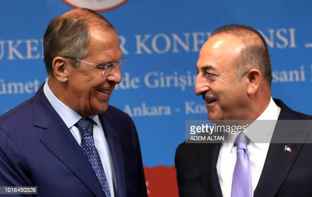 Turkey's Foreign Minister Mevlut Cavusoglu and his Russian counterpart Sergei Lavrov smile during a joint press conference following their meeting in...