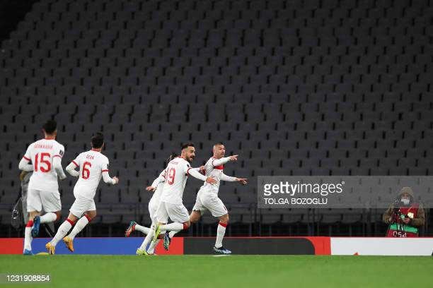 Turkey's forward Burak Yilmaz celebrates with teammates after scoring his second goal during the FIFA World Cup Qatar 2022 qualification Group G...