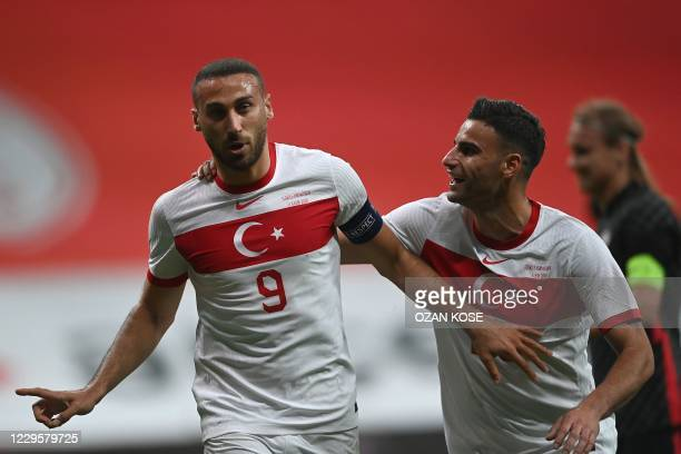 Turkey's forward Cenk Tosun celebrates with a teammate after scoring on a penalty kick during the friendly football match between Turkey and Croatia...