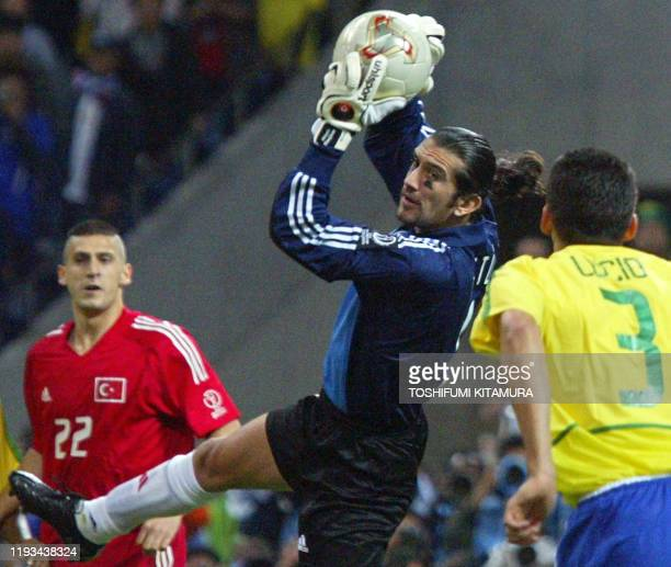 Turkey's goalkeeper Rustu Recber catches the ball while being watched by teammate midfielder Umit Davala and Brazil's defender Lucio during the...