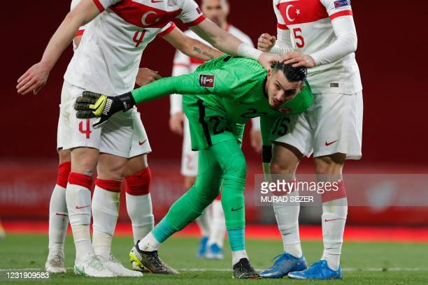 Turkey's goalkeeper Ugurcan Cakir is congratulated by teammates after saving a goal on a penalty kick during the FIFA World Cup Qatar 2022...