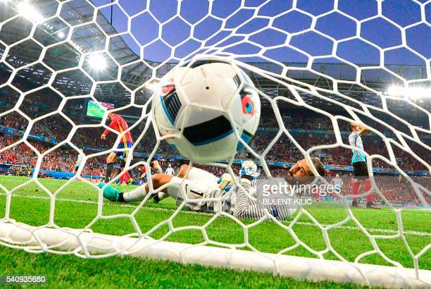 TOPSHOT Turkey's goalkeeper Volkan Babacan lays in his goal as Spain scores the 20 during the Euro 2016 group D football match between Spain and...