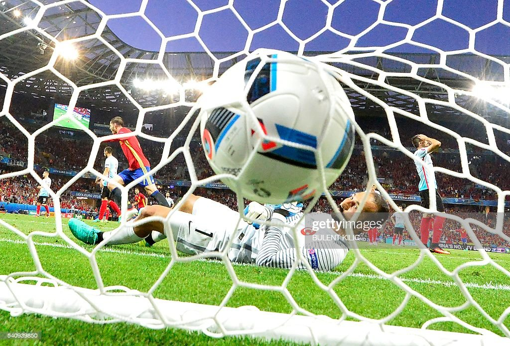 Turkey's goalkeeper Volkan Babacan lays in his goal as Spain's forward Alvaro Morata (L) scores the 1-0 during the Euro 2016 group D football match between Spain and Turkey at the Allianz Riviera stadium in Nice on June 17, 2016. / AFP / BULENT