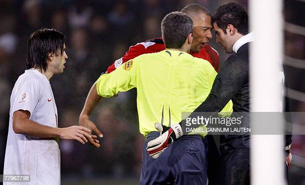 Turkey's goalkeeper Volkan Demirel and Norway's John Carew crush their heads against each other as refree Markus Merk and Gokhan Gonul look on during...