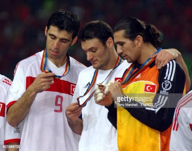 Turkey's Hakan Sukur Alpay Ozalan and Rustu Recber look at their third place medals