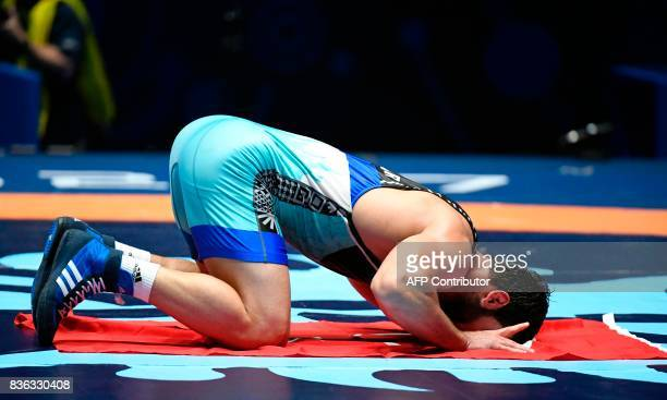 Turkey's Metehan Basar kisses the Turkish flag as he celebrates after winning the men's GrecoRoman style 85 kg category final of the FILA World...