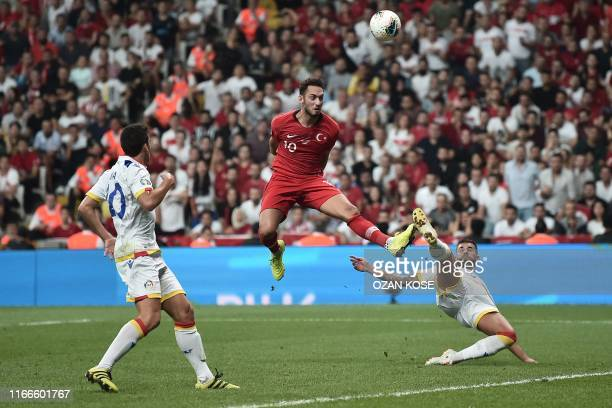 Turkey's midfielder Hakan Calhanoglu heads the ball next to Andorra's midfielder Ludovic Clemente and defender Marc Vales during the UEFA Euro 2020...