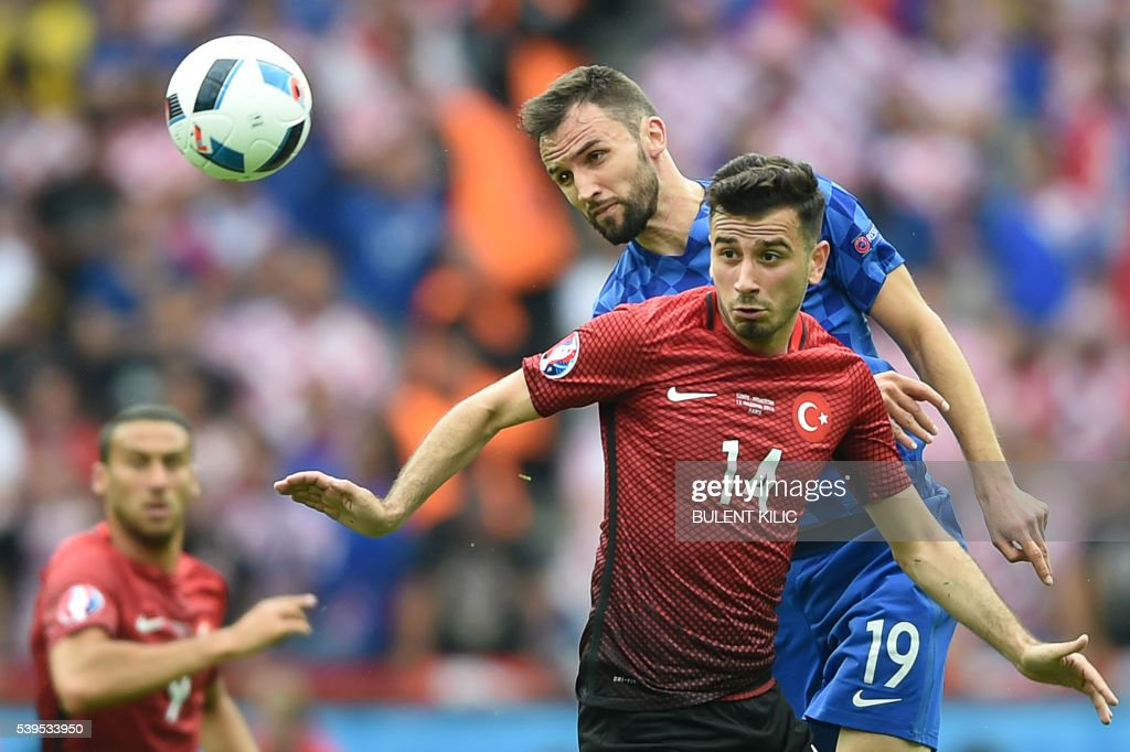 TOPSHOT - Turkey's midfielder Oguzhan Ozyakup (bottom) vies for the ball against Croatia's midfielder Milan Badelj during the Euro 2016 group D football match between Turkey and Croatia at Parc des Princes in Paris on June 12, 2016. /
