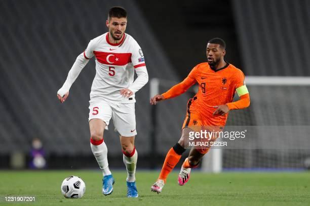 Turkey's midfielder Okay Yokuslu is challenged by Netherlands' midfielder Georginio Wijnaldum during the FIFA World Cup Qatar 2022 qualification...