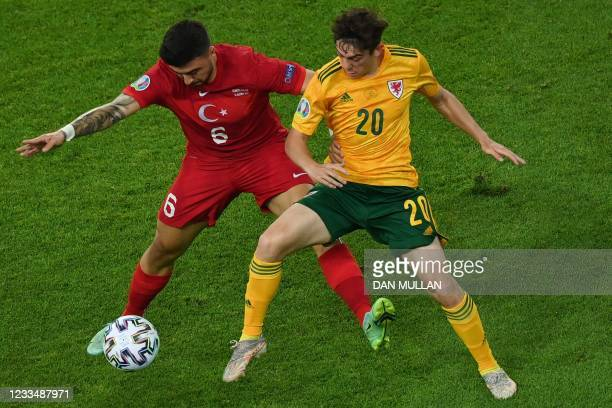 Turkey's midfielder Ozan Tufan is challenged by Wales' midfielder Daniel James during the UEFA EURO 2020 Group A football match between Turkey and...