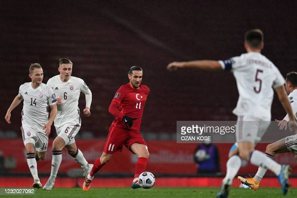 Turkey's midfielder Yusuf Yazici runs with the ball past Latvia's Andrejs Cigan?iks and Kristers Tobers during the FIFA World Cup Qatar 2022...