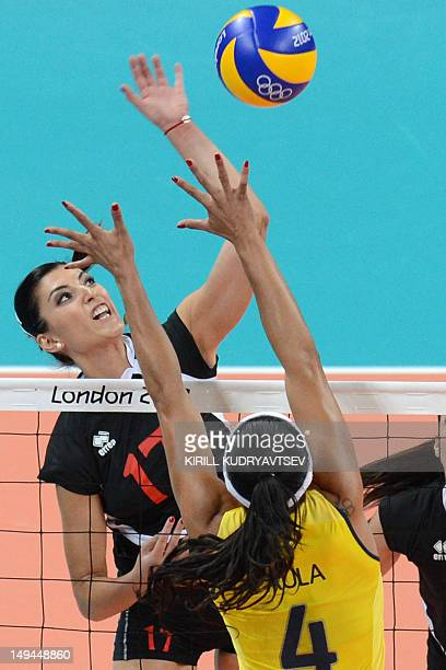 Turkey's Neslihan Darnel spikes as Brazil's Paula Pequeno attempts to block during the women's volleyball match between Turkey and Brazil in the 2012...