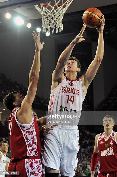 Turkey's Omer Asik jumps to score as Russia's Alexander Kaun tries to stop him during their World Championship preliminary round basketball game in...