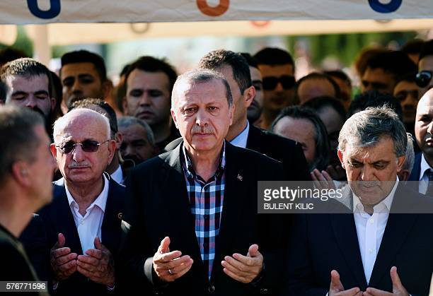 Turkey's President Recep Tayyip Erdogan and former Turkish president Abdullah Gul pray during the funeral of a victim of the coup attempt in Istanbul...