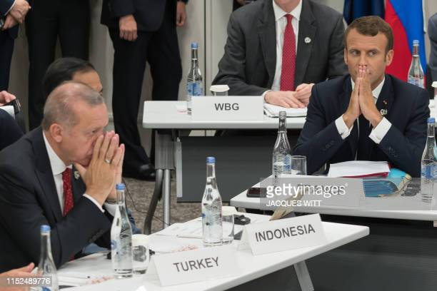 Turkey's President Recep Tayyip Erdogan and France's President Emmanuel Macron gesture as they attend a meeting on the digital economy at the G20...