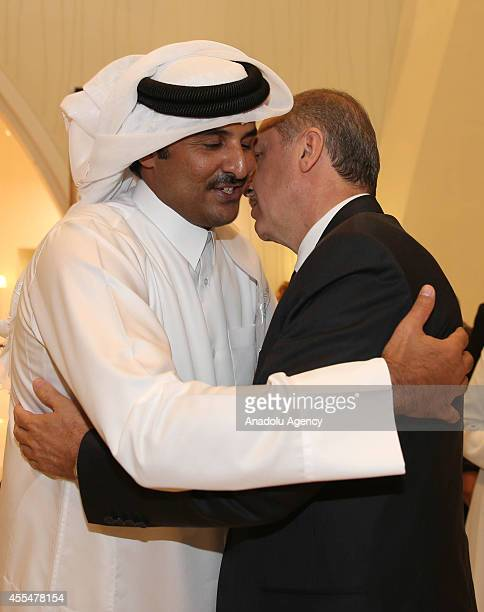 Turkeys President Recep Tayyip Erdogan and Qatar's emir Sheikh Tamim bin Hamad Al Thani shake hands during the groundbreaking ceremony of Turkish...