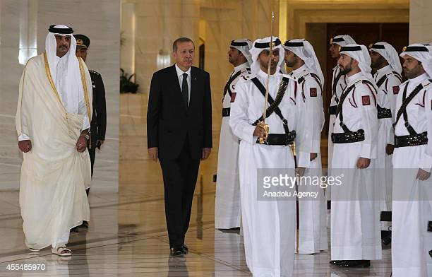 Turkeys President Recep Tayyip Erdogan and Qatar's emir Sheikh Tamim bin Hamad Al Thani inspect the honor guard during official welcome ceremony at...