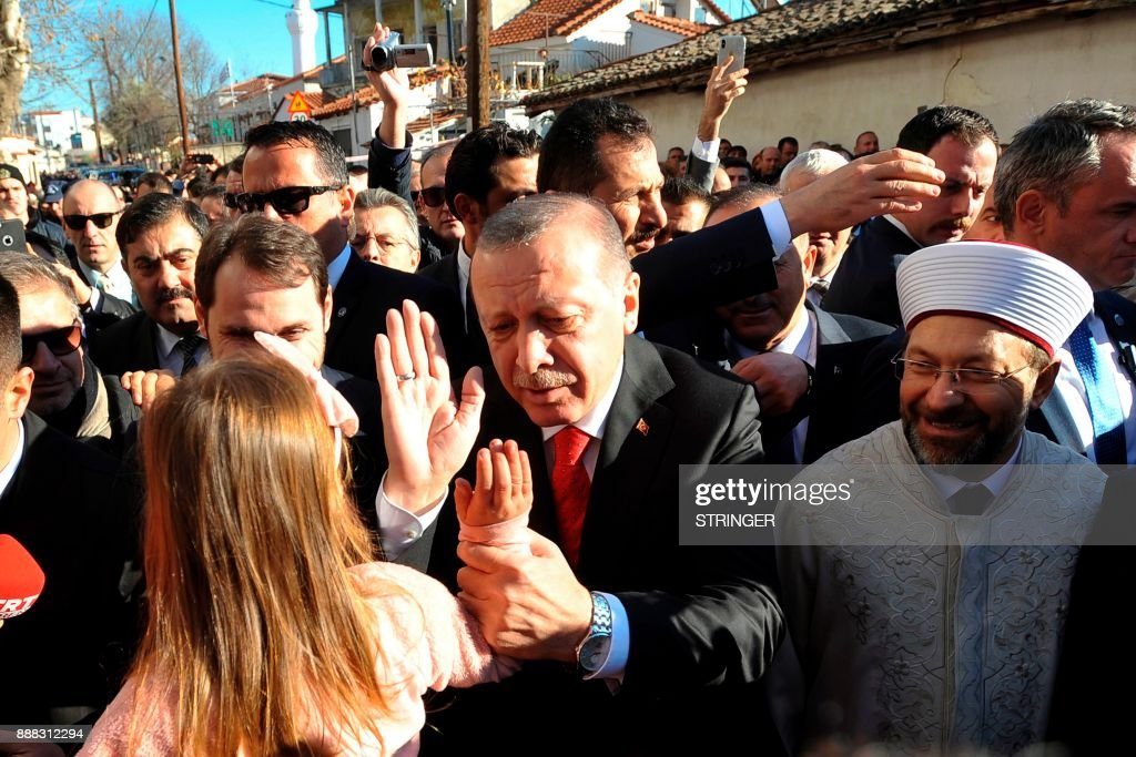 Turkey's President Recep Tayyip Erdogan (C) high fives a young girl on December 8, 2017 in the Komotini, northeast Greece. Turkish President Recep Tayyip Erdogan's trip two-day visit to Greece is the first by a Turkish head of state in 65 years. /