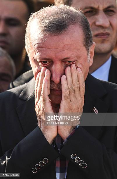 Turkey's President Recep Tayyip Erdogan reacts after attending the funeral of a victim of the coup attempt in Istanbul on July 17, 2016. Turkish...