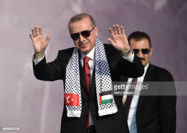 Turkey's President Recep Tayyip Erdogan salutes his supporters during a rally at Istanbul's Yenikapi fairground to show solidarity with Palestinians...