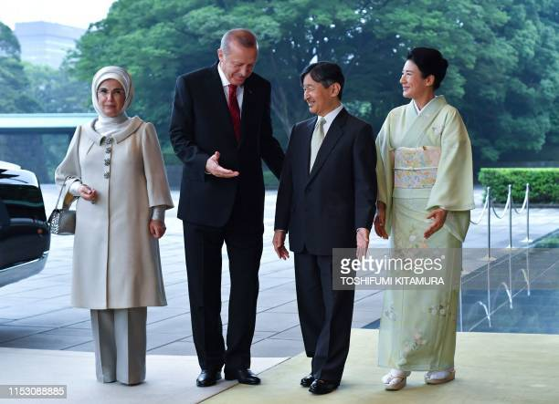 Turkey's President Recep Tayyip Erdogan speaks with Japan's Emperor Naruhito and Empress Masako beside his wife Emine Erdogan upon their arrival at...