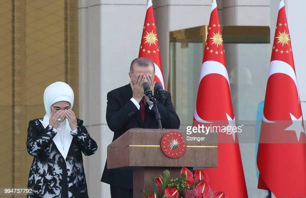 Turkey's President Tayyip Erdogan accompanied by his wife Emine Erdogan prays during a ceremony at the Presidential Palace on July 9 2018 in Ankara...