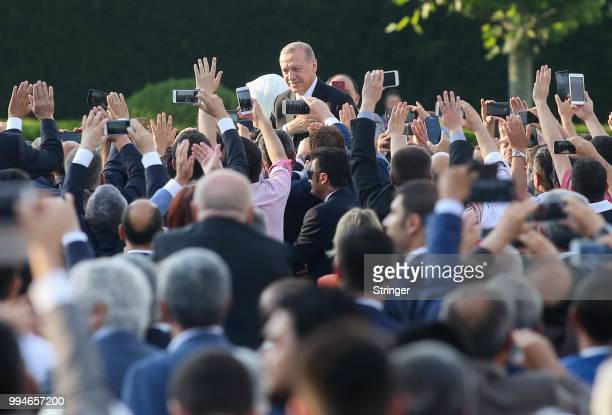 Turkey's President Tayyip Erdogan and his wife Emine Erdogan waves to supporters as they attend a ceremony at the Presidential Palace after Erdogan's...
