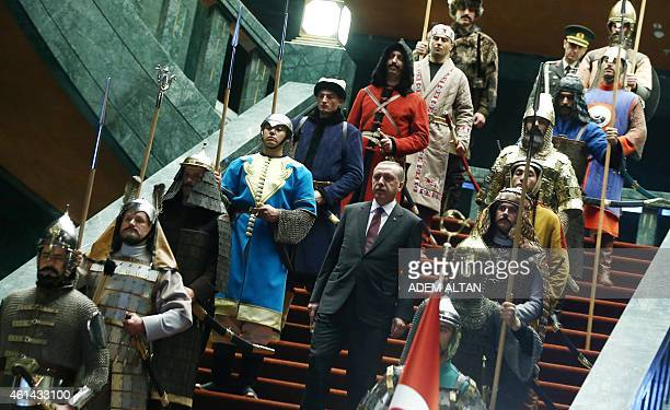 Turkey's President Tayyip Erdogan walks down the stairs in between soldiers, wearing traditional army uniforms from the Ottoman Empire, as he arrives...
