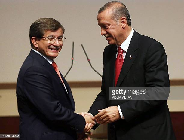 Turkey's presidentelect Recep Tayyip Erdogan shakes hands with Turkey's Foreign Minister Ahmet Davutoglu after he announced Davutoglu as new chairman...