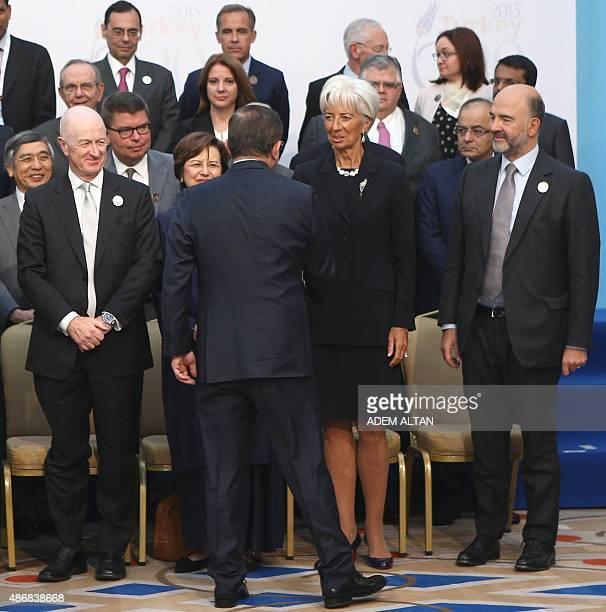 Turkey's Prime Minister Ahmet Davutoglu shakes hands with International Monetary Fund Managing Director Christine Lagarde next to European Economic...